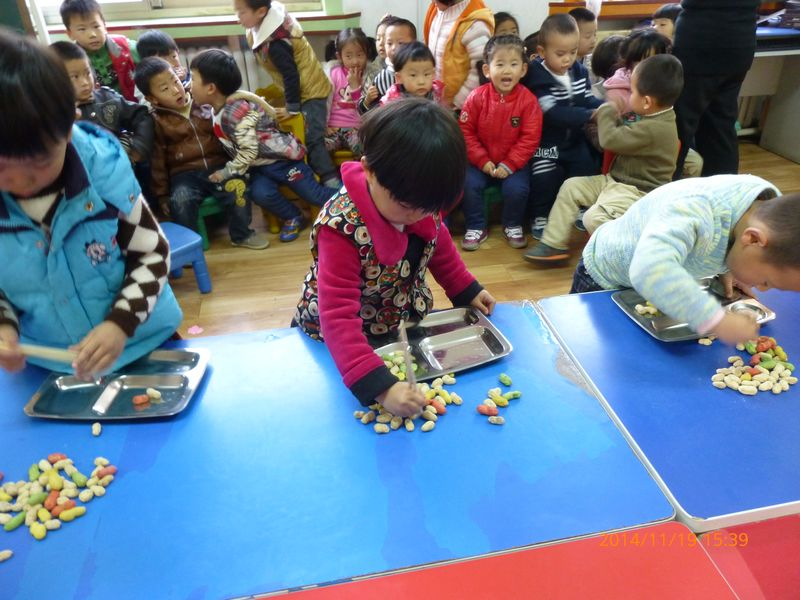 加油!加油!中二班传出此起彼伏的呐喊助威声,只见有些孩子手中的筷子如小鸡嘴,熟练地将桌子上的花生一个个叼到盘子中;有些幼儿小手肌肉发育不是很好,用筷子有些困难,花生已经快夹到盘子里了,却一不小心又掉了下去,但孩子毫不气馁,继续努力。一分钟之内看谁夹得最多,大家你追我赶,比赛场面好不热闹。老师们则举起手机,记录着孩子们的精彩瞬间。看到孩子们从不会拿筷子,到能熟练的夹花生,这样的进步让老师露出了欣慰的笑容。老师们把比赛照片第一时间通过微信平台传给家长,家长们也对此次活动报以积极地响应。